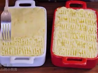 牧羊人派,把土豆泥分布在肉酱上面,用刮刀抹平,用叉子划出花纹,撒上奶酪丝