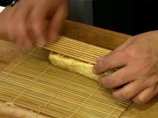 厚蛋烧,將煎好的厚蛋移至壽司竹簾上。趁熱利用竹簾將厚蛋包捲塑型,放置冰箱冷藏定型,食用時切小塊即可