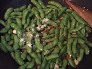 湖南香辣毛豆,加入适量盐,鸡精,生抽,老抽继续爆炒毛豆一段时间