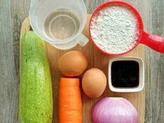 西葫芦鸡蛋饼,首先准备好,西葫芦,洋葱,胡萝卜,鸡蛋,面粉,水,盐胡椒粉, 蘸料准备,酱油10ml,米醋5ml.辣椒(粉)适量