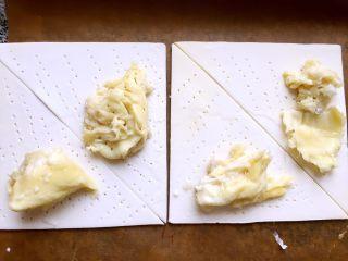 简易版的榴莲酥,酥皮室温稍稍软化,对切成三角形,用叉子扎些小洞,以免烘烤时鼓气,然后放适量榴莲肉。