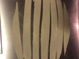 葱油面片,用刮板切成小条。