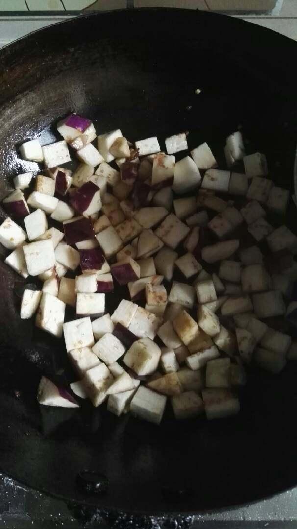番茄烧茄子,锅内放油,倒入茄子炒软变黄。