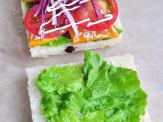 蔬菜总荟三明治,在最上层铺上切片的蕃茄,挤一层沙拉酱,另一片面包也是挤一层沙拉酱,铺一层生菜 。