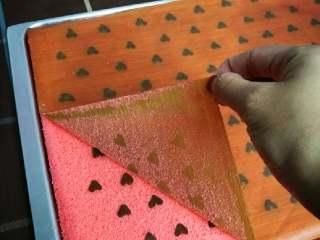 织女也疯狂 — 【爱心蛋糕卷】,将戚风蛋糕倒在铺油纸的烤盘上,撕去表面油纸,换一张新油纸,再倒扣过来,爱心面朝下。