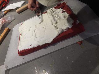 红丝绒蛋糕卷,蛋糕卷稍晾凉后用抹刀把打发好的奶油铺在蛋糕卷上,四边薄中间厚