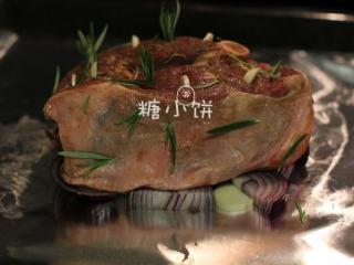 【迷迭香烤羊腿】中西混搭版,将洋葱和剩余的蒜片铺在锡纸上,再把羊腿架在洋葱片上