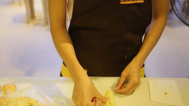 不一样的黄金月饼酥,松弛好的面团,收口朝上,用拇指在面卷中间压一下,两边往上折,压平
