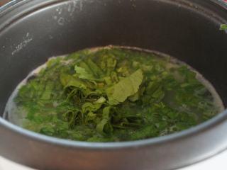 电饭锅芥菜肉粥,粥煮好了,加入芥菜。搅拌均匀,大致把芥菜煮软