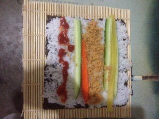 肉松寿司,将帘子平铺,拿一张海苔放在帘子上,放米饭、调味萝卜、胡萝卜、黄瓜、肉松!根据自己的口味放入酱(番茄酱、沙拉酱、鱼子酱……)