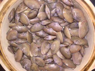 酒蒸蛤蜊,倒入蛤蜊,盖上锅盖
