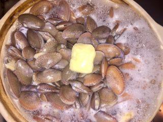 酒蒸蛤蜊,再煮至沸腾,加入一小块黄油,加盖。