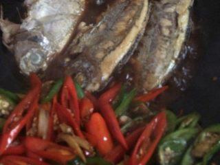 海鱼美味中餐,把青椒,红椒放置锅的另一边,把鱼放到有汤汁的地方,让它入一下味。