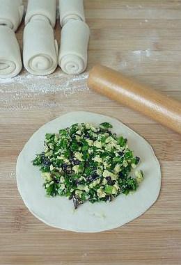 韭菜盒子馅不出水的妙招,然后取一个小面卷,擀开成饺子皮一样的圆形薄面片,上面放一大勺韭菜馅。