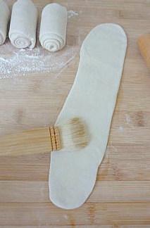 【葱油饼】,然后取一个小面卷,擀开成细长的薄面片,上面用软毛刷轻刷一层薄油。