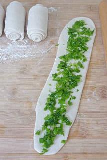 【葱油饼】,撒上少许盐抹匀,再撒上葱花,边缘部分留出空隙。盐一定得放,和面时放的少。