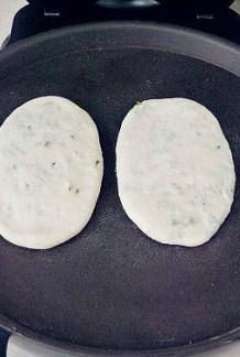 【葱油饼】,放入预热好的电饼铛,盖上盖子,1-2分钟后掀开翻面。