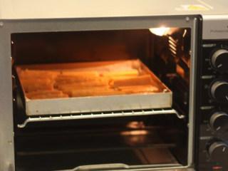 【桂花蜂蜜红薯条】,烤箱上下火200度预热好,把红薯条放入烤箱中层,烘烤15分钟