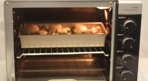 【蒜香番茄烤鸡腿】,把烤盘放进烤箱中层,200度烤烤60分钟