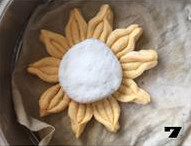 【向日葵面点】,取白色面团揉匀,分成四份揉圆后轻轻按扁放入向日葵花瓣正中。