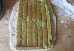 体会不一样的口感----绿茶蛋糕面包,再将面团擀成长条,将刚刚完成的蛋糕一分为二,将一块放在长条的面团上;