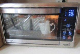 体会不一样的口感----绿茶蛋糕面包,将模具放入烤箱中,放入一杯开水,在烤箱中完成二次发酵;