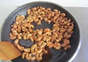 自制健康小零食--芝麻腰果,待其颜色变为棕色后放入准备好的腰果进去翻炒;