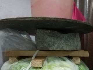 东北酸菜,白菜上放木头条固定,再压上大石头或别的有一定重量的东西。