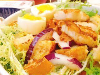法风煎鱼排沙拉,鱼排切块,摆盘,苦莒上面摆上法棍,鱼排,鸡蛋,撒上欧芹碎,百里香。