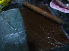 可可曲奇卷,将两份面团分别用保鲜袋包住,用擀面杖擀成4毫米左右的薄片。