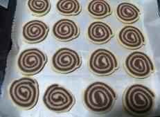 可可曲奇卷,取出面棍,用刀切片,厚薄可根据个人喜好而定,然后排入铺好烤纸或者油布的烤盘上。烤箱预热180度,中上层,烤10至12分钟即可。