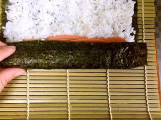 家庭版简单寿司,6、三分之一处铺上火腿条、黄瓜条、胡萝卜条,随意哈 7、卷起来,手上带点劲儿别让寿司卷太松