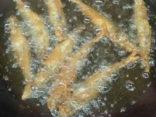 椒盐多春鱼,多春鱼撒上味精,裹上脆浆,下油锅炸至熟透金黄色捞出。
