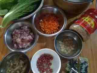 芥菜咸饭,材料备齐。大米提前泡20分钟,蛤蜊干和干贝也提前泡发洗净沙子,芥菜清洗干净。五花肉洗净控干切长细条,胡萝卜切丁,葱白、生姜各切末