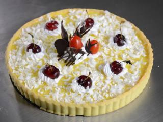布丁水果派,将冻好的布丁派用鲜奶油、巧克力件、樱桃、圣女果、白巧克力碎装饰好即可。