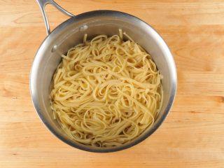 鲜虾奶油意面,面条放入沸水煮9-10分钟,捞出滤水然后放入锅中,加入2茶匙橄榄油然后搅拌均匀,防止面条粘在一起。