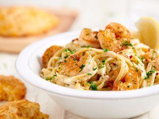 鲜虾奶油意面,将酱汁和虾倒入装有意大利面的锅中搅拌均匀,将意面装在一个盘子里,再用柠檬块和剩余的香菜点缀即可。
