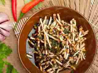 #年夜饭#凉拌鱼腥草,取一大碗,放入鱼腥草和野蒜,浇上调好的酱汁拌匀。