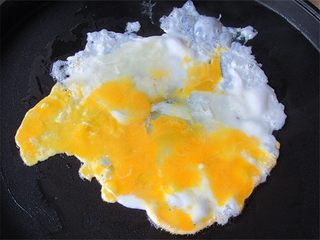 老妈酱香鸡蛋单饼卷,电饼铛里打入鸡蛋一个,摊开来