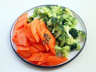 胡萝卜炒西兰花,西兰花洗净后分成小朵,胡萝卜切成菱形片。姜和蒜也改刀备用。