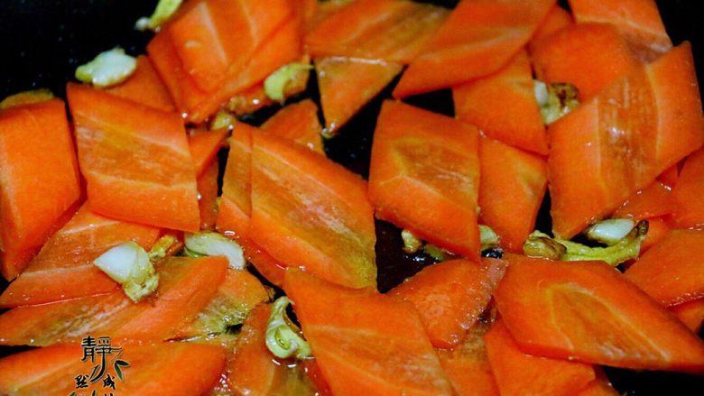胡萝卜炒西兰花,先放胡萝卜小火翻炒,添加适量清水防止锅干。