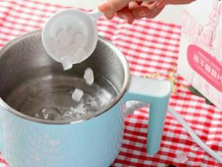 小伙伴们赞不绝口的冰糖玫瑰草莓炖,将冰糖放入沸水中,搅拌至溶化;