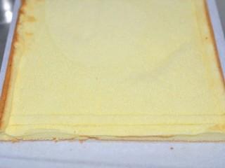 草莓奶油蛋糕卷,将蛋糕倒扣在油纸上撕掉油布,盖一张油纸让蛋糕片晾凉,将蛋糕前边不整齐的边切掉轻划二刀,尾部斜切。