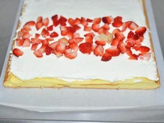 草莓奶油蛋糕卷, 蛋糕片上涂上打发好的淡奶油,涂的时候要前端厚后端薄,均匀地撒上草莓粒,用擀面杖包着油纸将蛋糕卷卷起来,冰箱里冷藏二个小时,定型后切片即可。