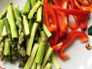 芦笋炒里脊+#春意绿#,芦笋洗净切段,甜椒去蒂去籽,切成条。