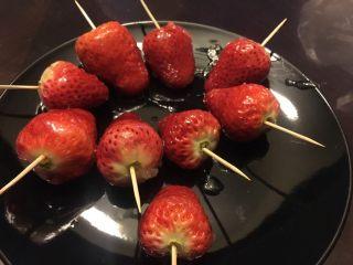 零失败冰糖草莓串,后面就没时间拍照了。熬到冰糖融化,水份完全蒸发,只剩糖的时候,转小火,用牙签串上草莓裹糖水,放到盘子里摆开。我放的太近了,会粘黏在一起。记住,全程不要关火,不然糖在锅里也会粘黏。动作要快,不然糖会糊。