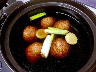 红烧狮子头,把丸子放进容量大的砂锅,把姜切片放进去,葱段、蚝油、冰糖、红烧酱油也放进去,添加足够的清水。