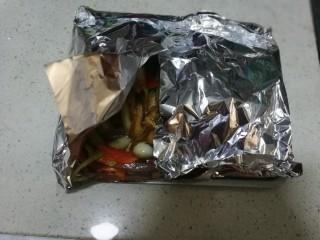 锡纸包烤鲈鱼,把锡纸从四周卷包好,要注意四角不要漏出汤汁