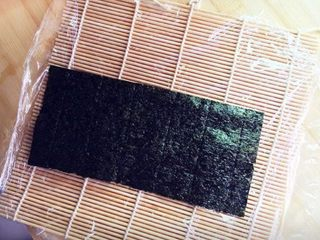 樱花寿司,首先将寿司帘上铺上保鲜膜,再放上一片海苔。