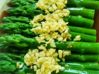 蒜香芦笋,将炒好的大蒜末放在芦笋上